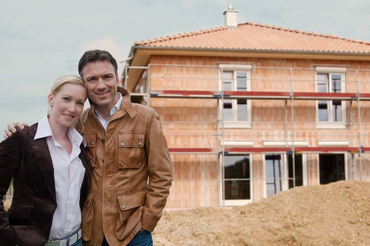 Paar vor neugebautem Eigenheim