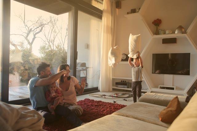 Glückliche Familie spielt im Wohnzimmer nach erfolgreichem Blower Door Test und damit sichergestellter Luftdichtheit