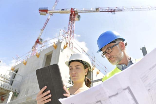 Bauleiter stehen mit Bauunterlagen vor einem Rohbau